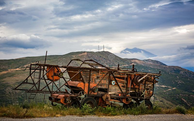 Rusting and decaying combine harvester abandoned on mountain roadside with dramatic mountains behind royalty free stock photo