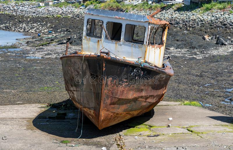 Rusting derelict boat left on a beach stock photos