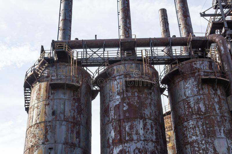 Rusting derelict steel mill blast furnaces with catwalks royalty free stock photography