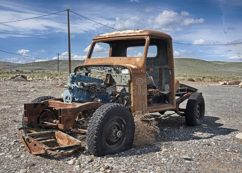Rusting Pickup Truck In Parking Lot. A solitary old pickup truck, abandoned in a gravel parking lot and exposed to the elements in Eastern Washington, is rusting royalty free stock image