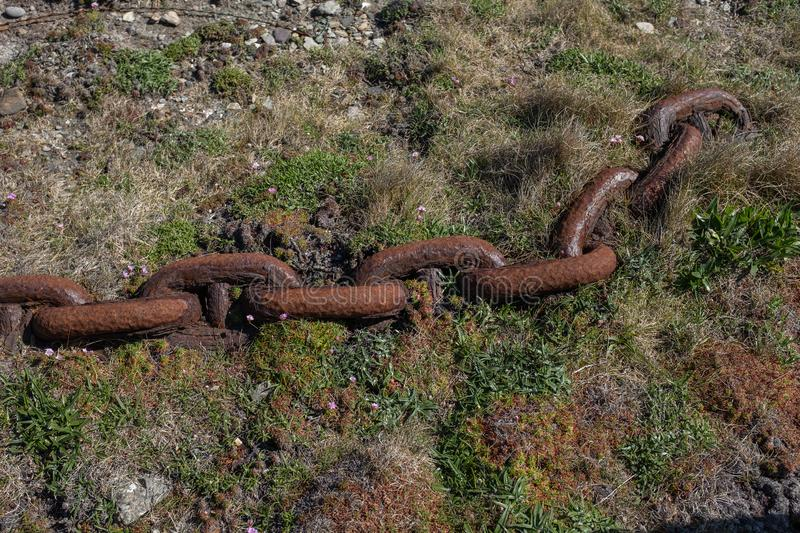 A rusting ship& x27;s anchor chain decaying into the ground stock photography