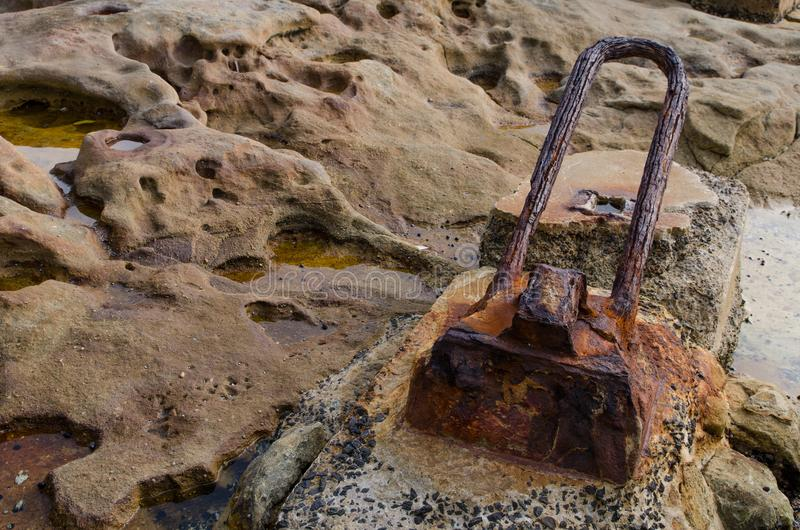 Rusty abandoned boat cleats on the rocky coastline in Australia. A Rusty abandoned boat cleats on the rocky coastline in Australia royalty free stock photos