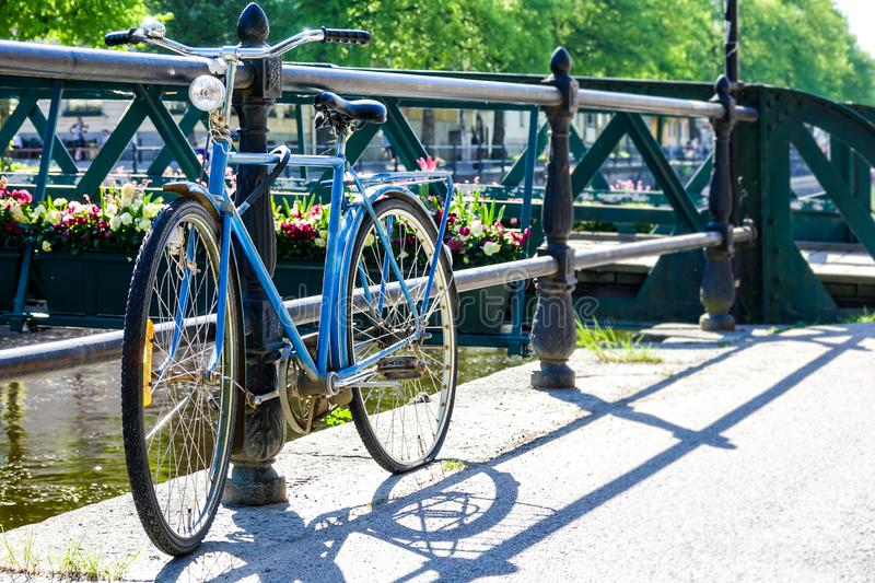 Rusty abandoned vintage retro bike parked by a bridge. Over a river. Blue bicycle with a flat tire and flowers in the background stock image