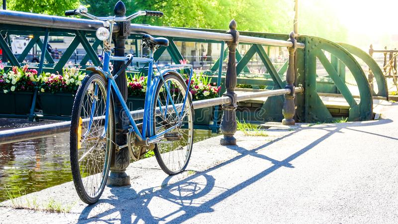 Rusty abandoned vintage retro bike parked by a bridge. Over a river. Blue bicycle with a flat tire and flowers in the background royalty free stock photos