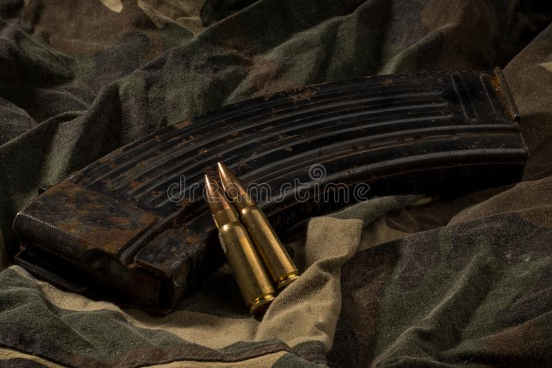 Rusty AK-47 magazine and bullets on camouflage textile background stock image