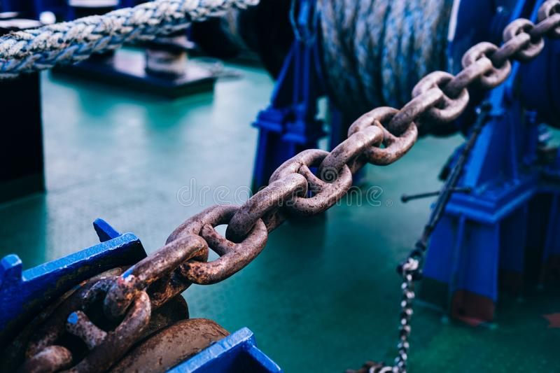 Rusty anchor chain on the bow. Part of mooring equipment. Blur. Close-up. Background stock photos