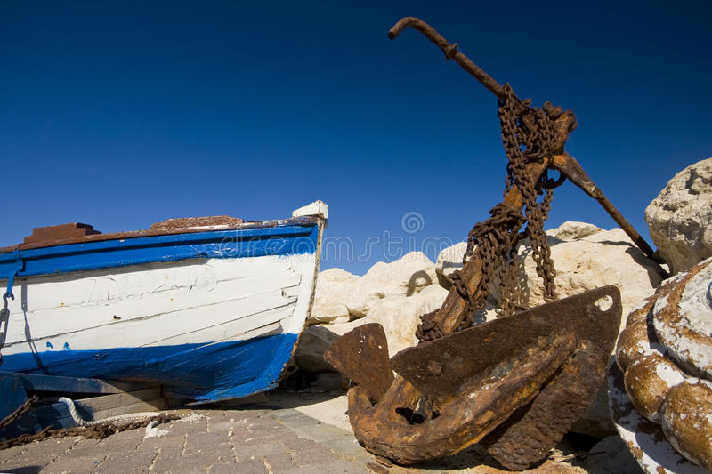 Rusty anchor and an old boat stock image