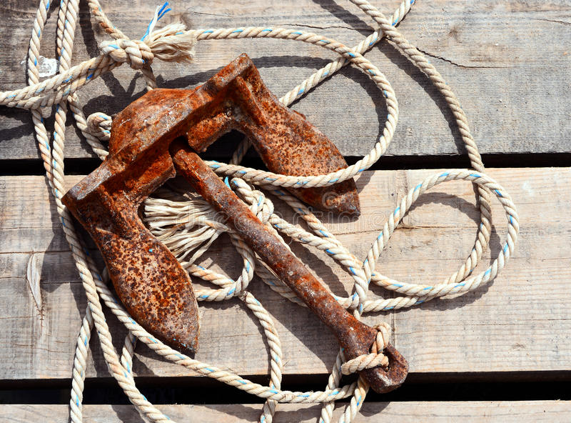 Rusty anchor. And rope lying on wood royalty free stock image