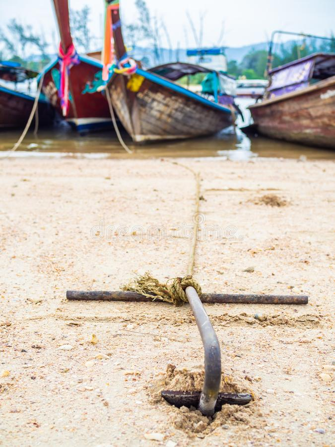 Rusty anchor on the sand beach with traditional long tail boat. On the sea in Thailand vertical style royalty free stock photo