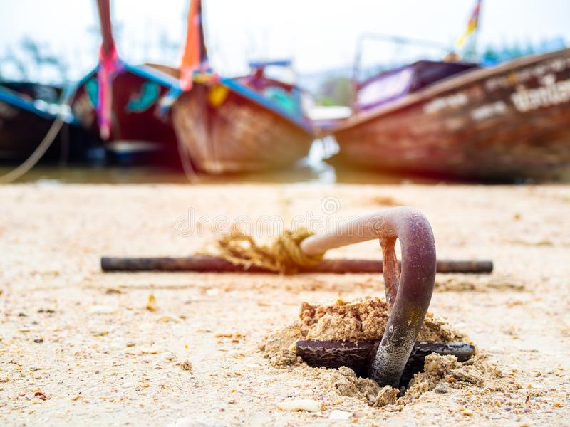 Rusty anchor on the sand beach with traditional long tail boat. On the sea in Thailand stock images
