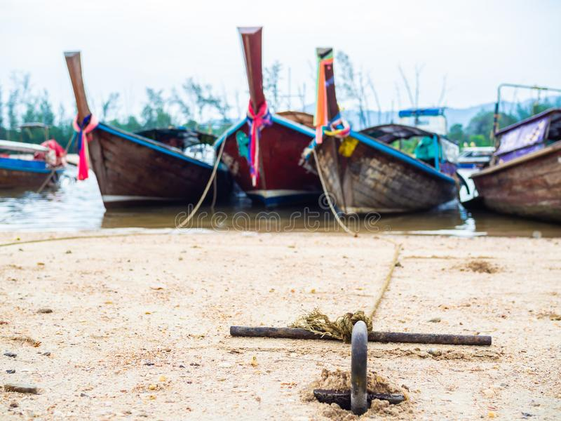 Rusty anchor on the sand beach with traditional long tail boat. On the sea in Thailand stock image
