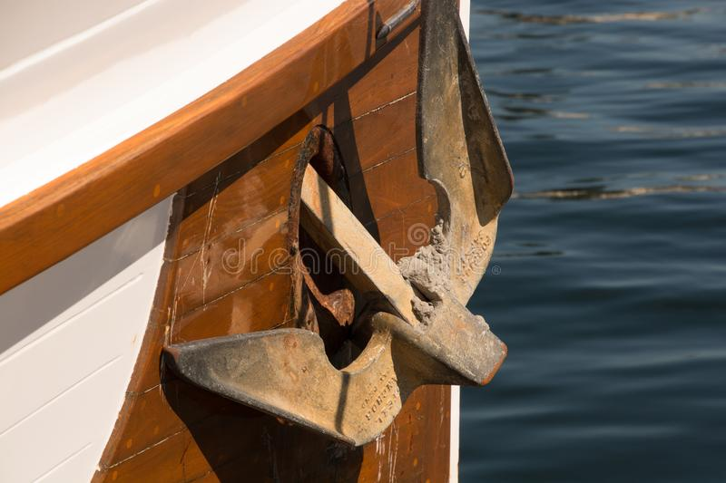 Rusty anchor on a wooden boat. A rusty anchor on a wooden boat on a sunny day in Roche Harbor, WA stock image