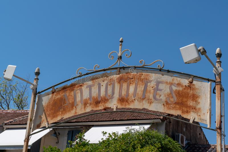 Rusty Antiques Shop Sign means Antiquites in French city isle sur la sorgue stock image