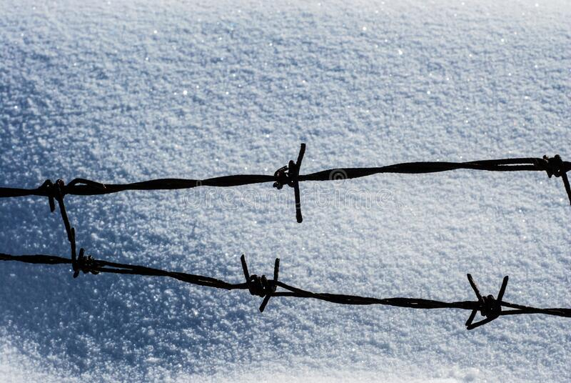 Rusty barbed wire fence against the snow. Winter scene in mountains on cold day. Landscape. Rusty barbed wire fence against the snow. Winter scene in mountains stock image