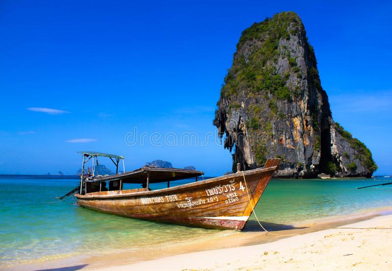 Rusty boat on the beach on the background of crystal clear sea water , blue Sunny sky and gray green rocks. Turquoise lagoon in stock photos