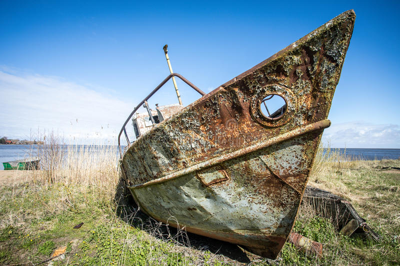 Rusty boat. Old abandonment rusty boat lying on grass royalty free stock photography