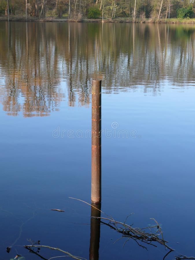 Rusty Bollard em um lago fotografia de stock