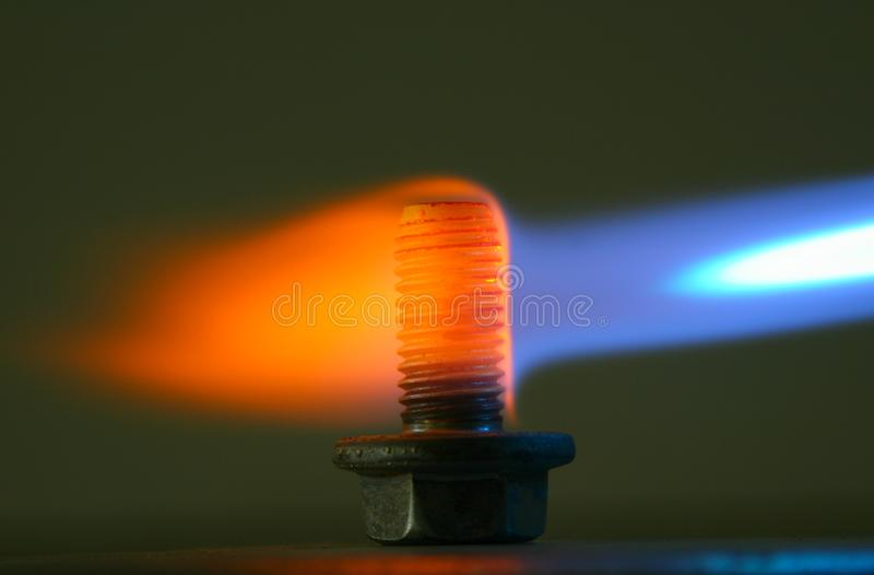 Rusty bolt in a flame of a gas torch. stock photos