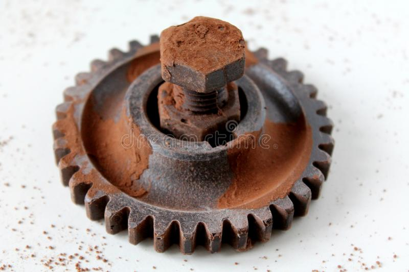 Rusty bolt, nut and gear wheel made of chocolate isolated on white background stock image