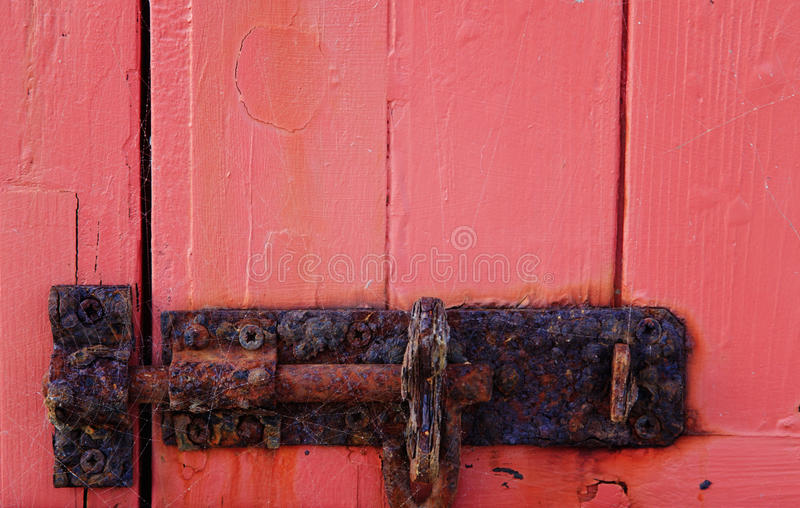 Rusty bolt. Old rusty bolt on a red wooden door royalty free stock photos