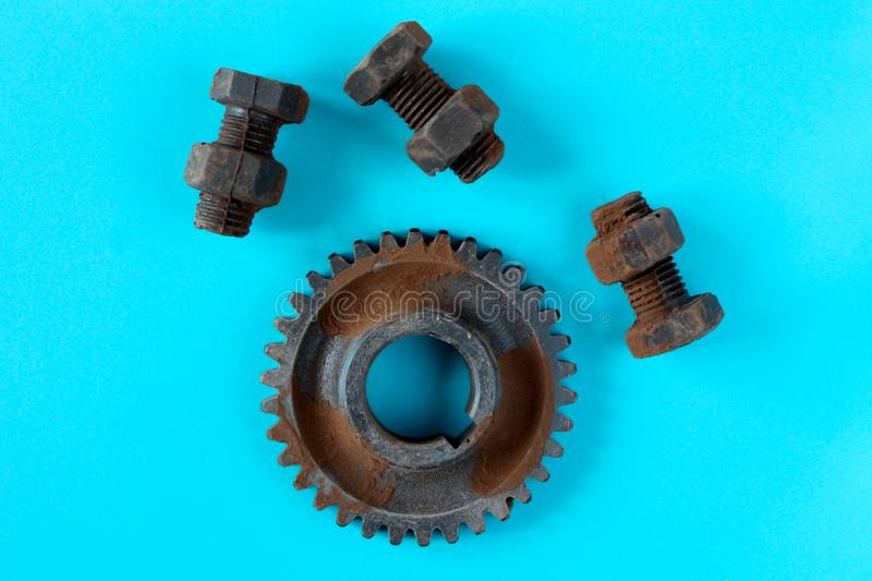 Rusty bolts, nuts and gear wheel made of chocolate isolated on blue background royalty free stock photos