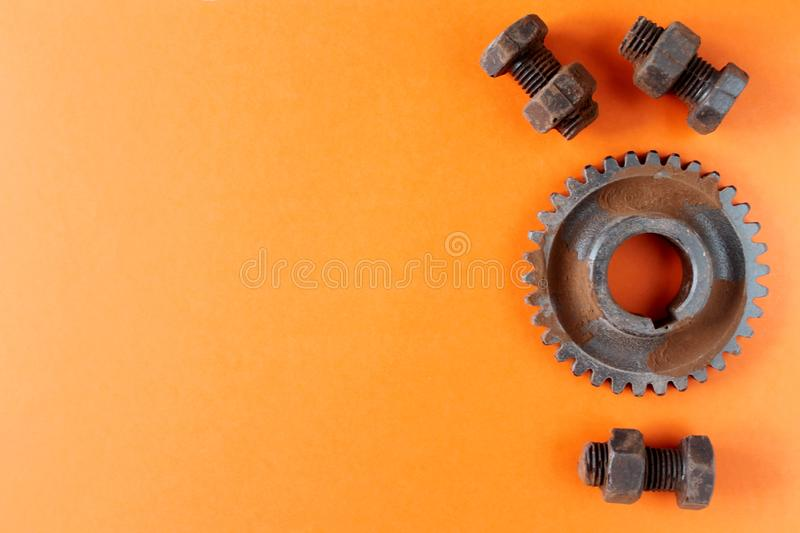 Rusty bolts, nuts and gear wheel made of chocolate isolated on orange background royalty free stock photos