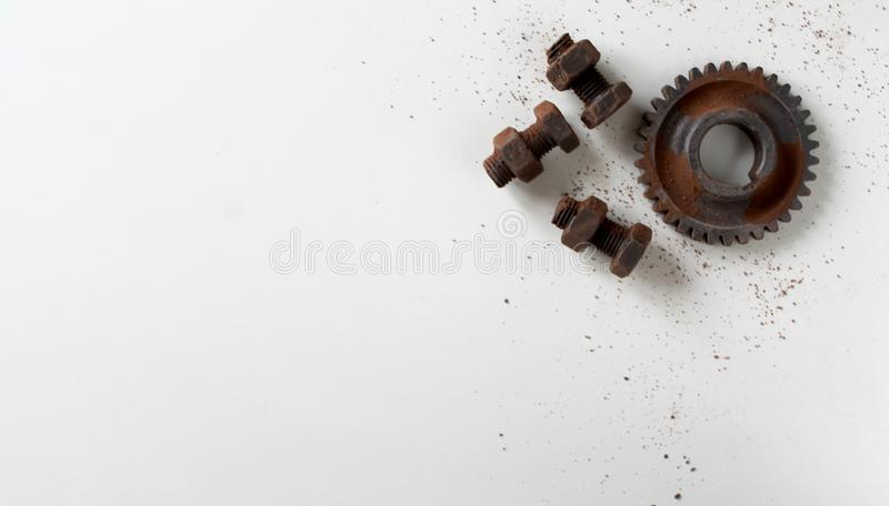 Rusty bolts, nuts and gear wheel made of chocolate isolated on white background royalty free stock images