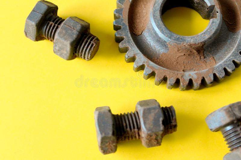 Rusty bolts, nuts and gear wheel made of chocolate isolated on yellow background stock photography
