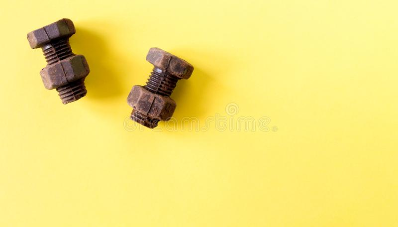 Rusty bolts and nuts made of chocolate isolated on yellow background. Mechanic gearing background. Father`s day card obects. Copy space for text royalty free stock photos