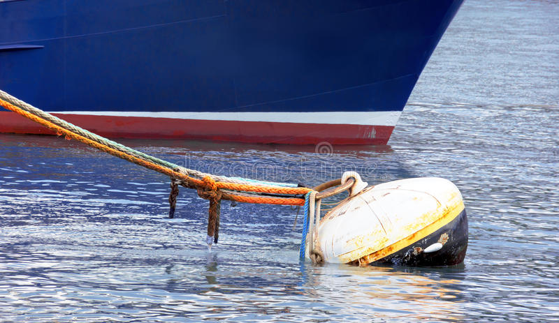 Rusty buoy with lot of ropes and a ship stock photos