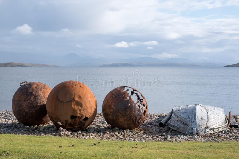 Rusty buoys on the beach at Polbain, north of Ullapool, on the west coast of Scotland. Summer Isles in background stock photography
