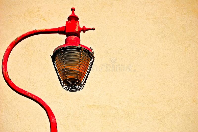 Rusty cast iron street lamp against cream painted textured wall royalty free stock photos