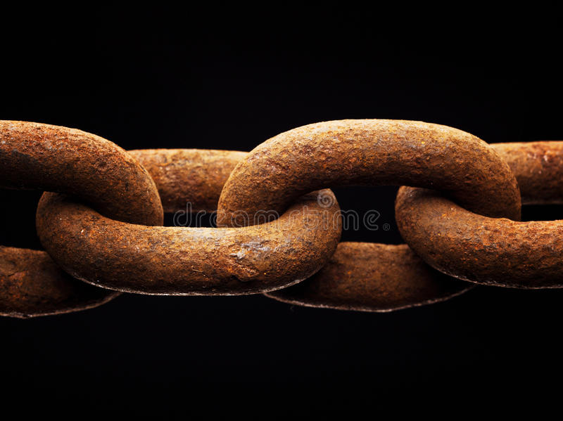 Rusty chain. Macro rusty brown links of chain, isolated on black background royalty free stock photos