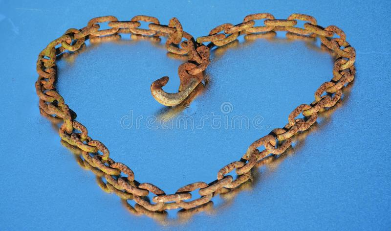 Rusty chain heart and dew. A heart like form made by a rusty and old chain on a blue background that reflects the blue of the sky. It suggests that hate can royalty free stock image