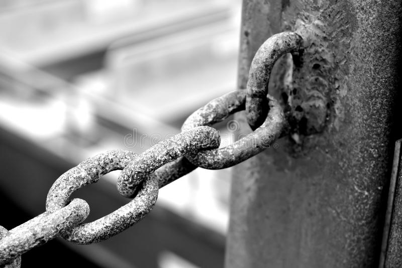 A rusty chain hooked on a metal pole stock images