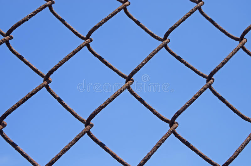 Rusty Chain Link Fence. Detail of a rusty chain link fence with blue sky background royalty free stock image