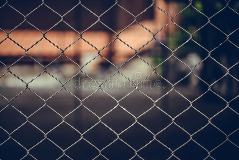 Rusty Chain Link Fence of steel netting on blur background. Wired metal fence in vintage tone royalty free stock photos