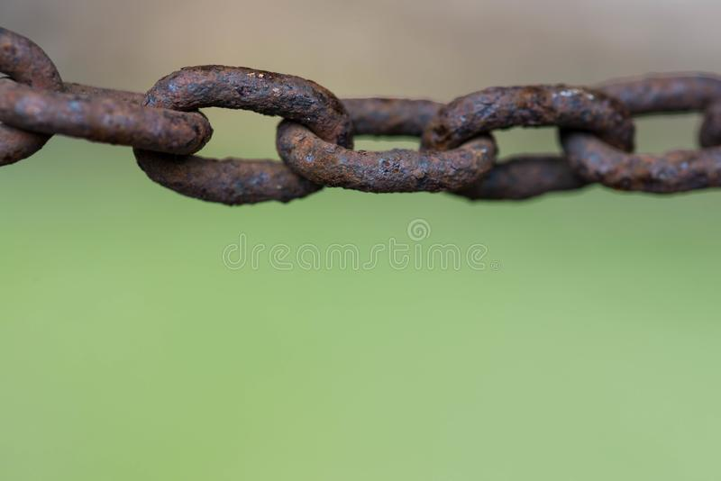 Rusty chain links close up macro shot on green natural background. Copy space stock photography