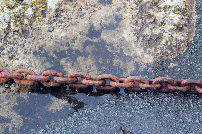 Rusty chain on a quay side. A strong rusty chain on the side of a dock securing a boat royalty free stock image