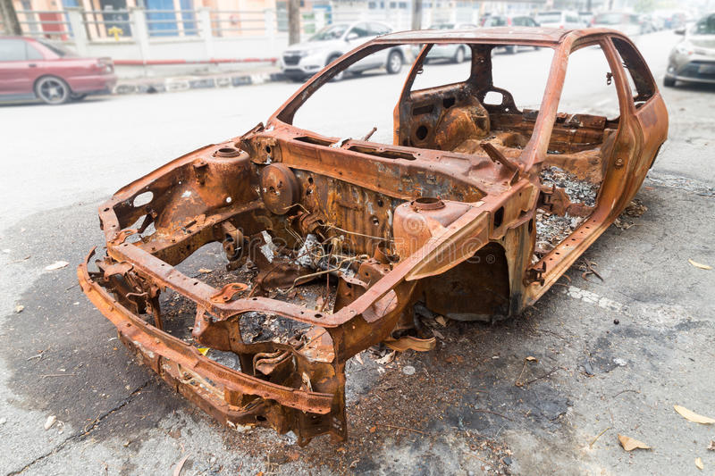 Rusty chassis of a burnt car abandoned by the side of the street stock image