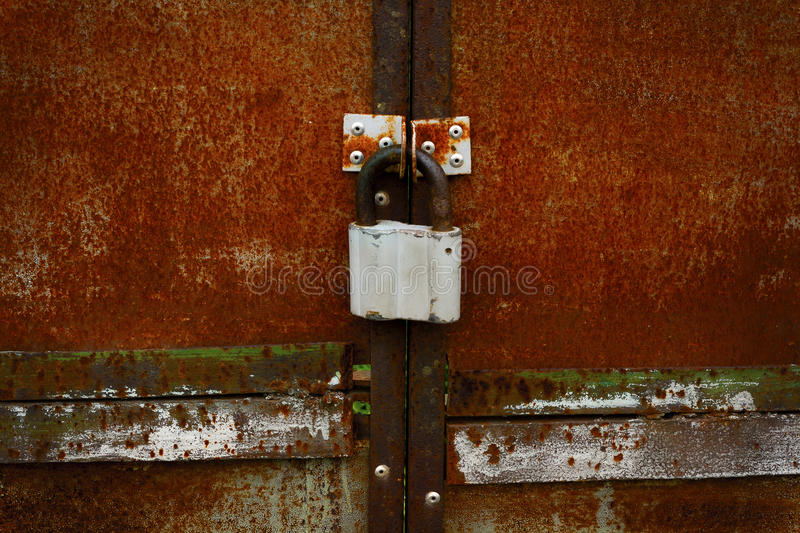 Rusty closed doors with old fashioned padlock. Rusty closed and colored doors with old fashioned padlock stock image