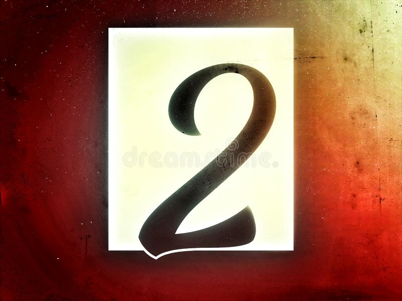 On the rusty color background the number two on the white sticker. Number 2 in black color on the shine and letter stock photography