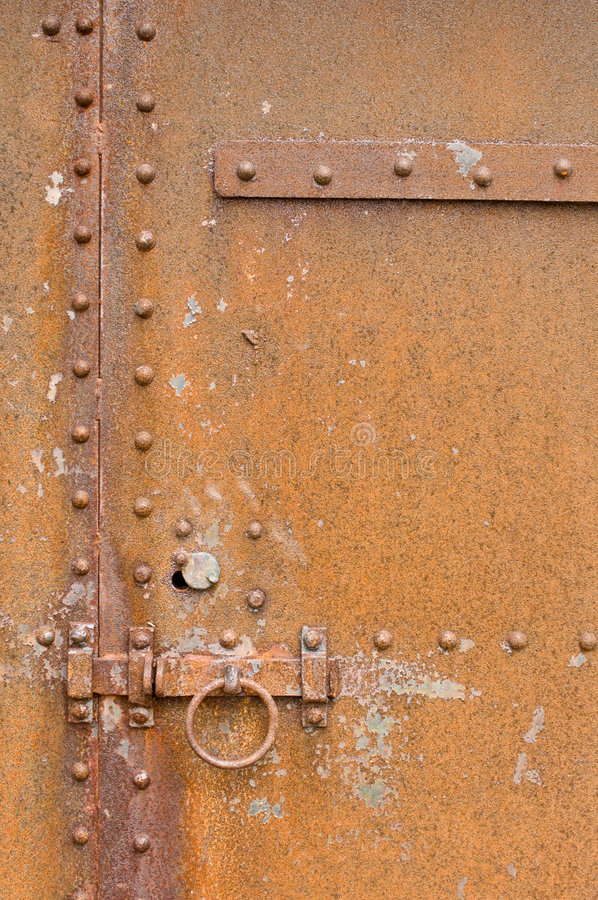 Rusty, corroded old metal door, latch and bolts stock photography