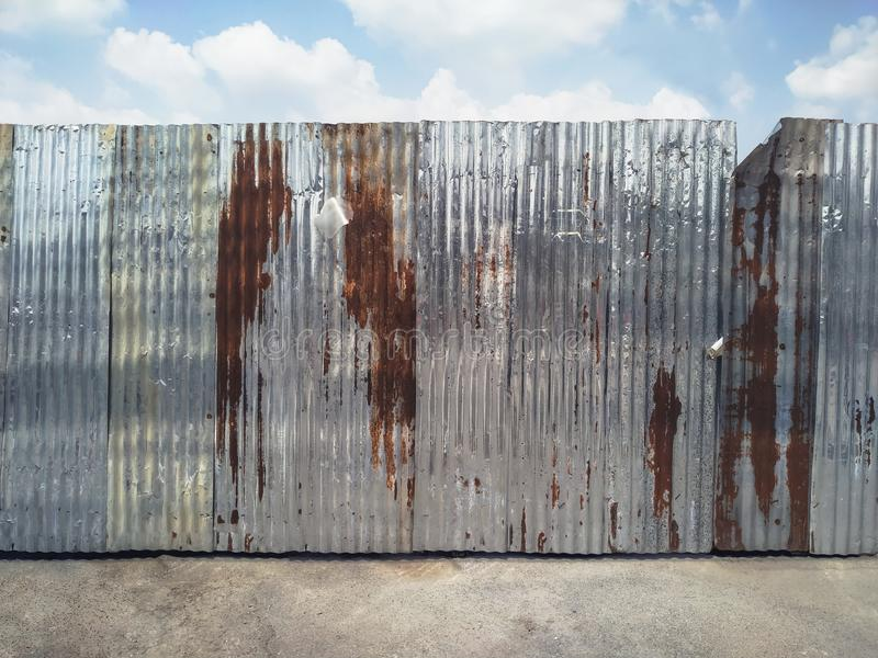 Rusty corrugated metal fence. Old rusty corrugated metal fence of construction site stock photos