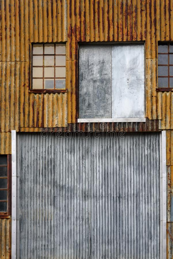 Rusty corrugated metal wall, with windows and doors, of an old building at the abandoned Grytviken whaling station, South Georgia. Rusty corrugated metal wall royalty free stock photography