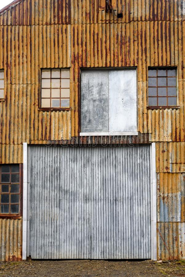Rusty corrugated metal wall, with windows and doors. Of an old building at the abandoned Grytviken whaling station on South Georgia, Antarctica stock photography