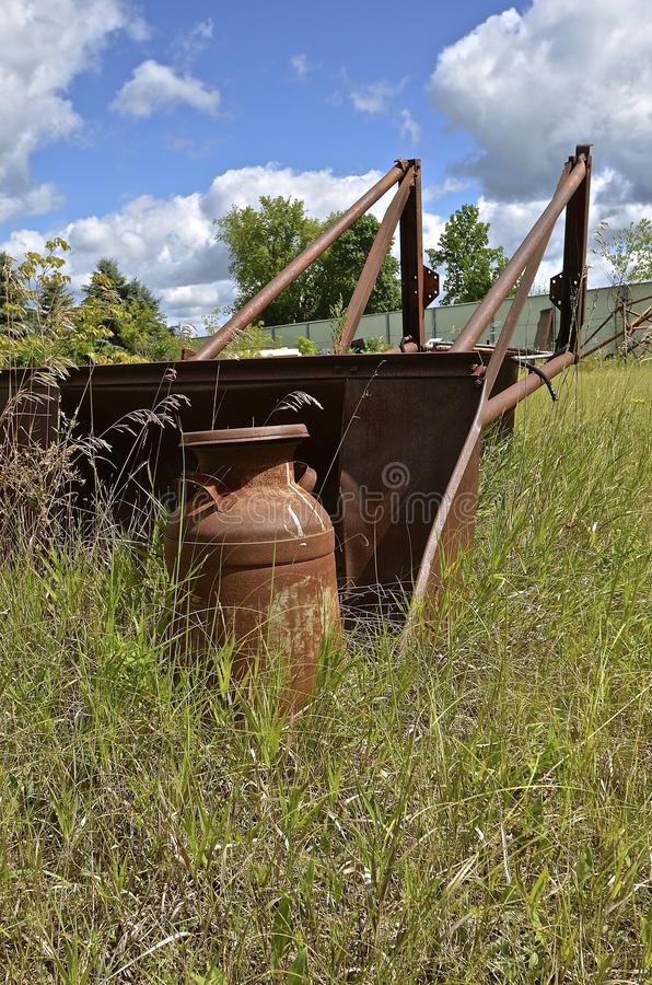 Rusty cream can by an old front end loader. A rusty cream can is left in a weedy pasture by an old front end loader stock images