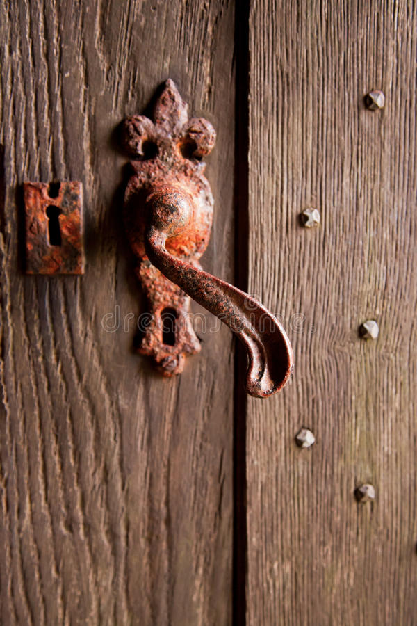 Rusty door handle. A curved and rusty door handle and lock on a studded wooden doorway on an ancient English coastal chapel royalty free stock images