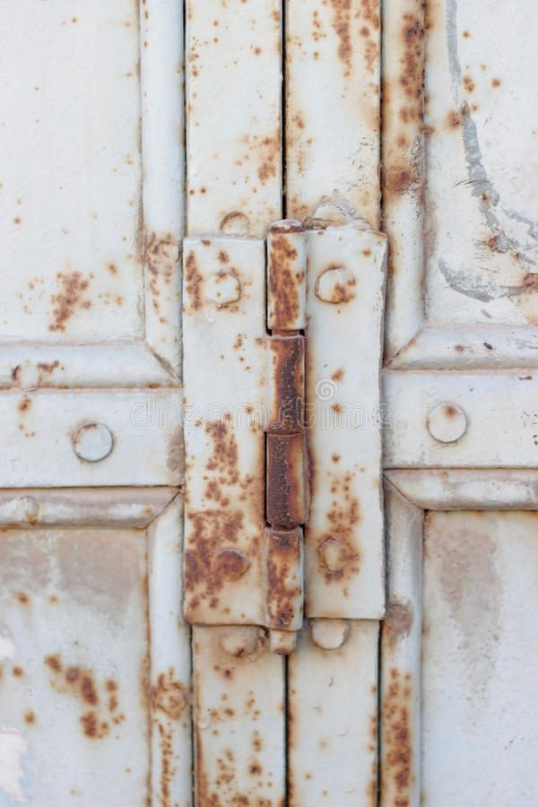 Rusty door hinge with rust, crack and old loose white paint texture stock photo