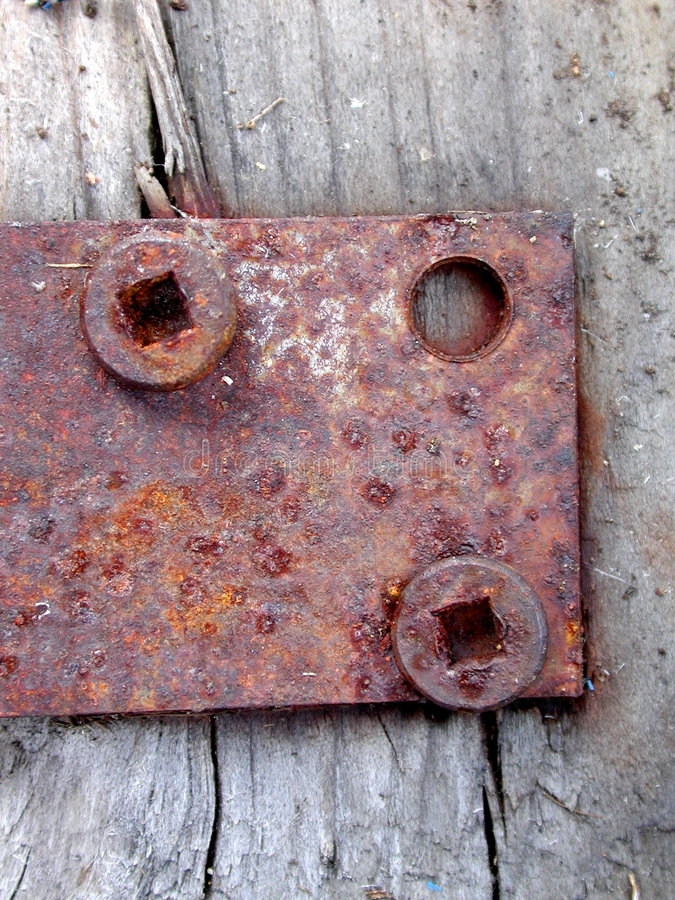 Rusty Door Hinge Screws Wood. An old rusty door hinge with 2 screws loose and one missing on the side of an old faded barn royalty free stock image